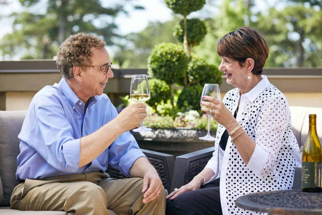 Peachtree Hills place 55+ active-adult community rooftop with a couple toasting happiness at living there.